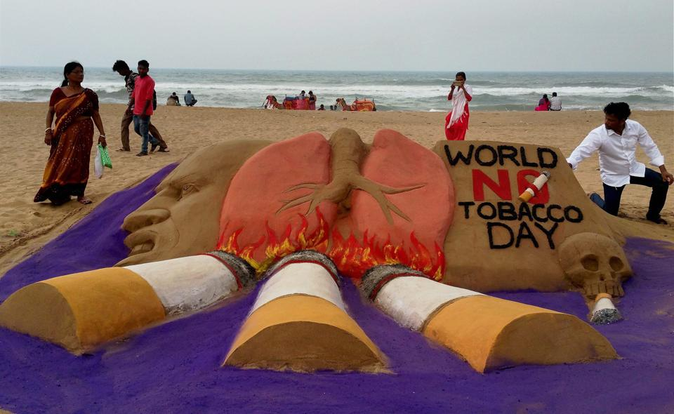 Sand artist Manas Sahoo creates a sand sculpture on eve of 'World No Tobacco Day', in Puri, on Tuesday. (PTI)
