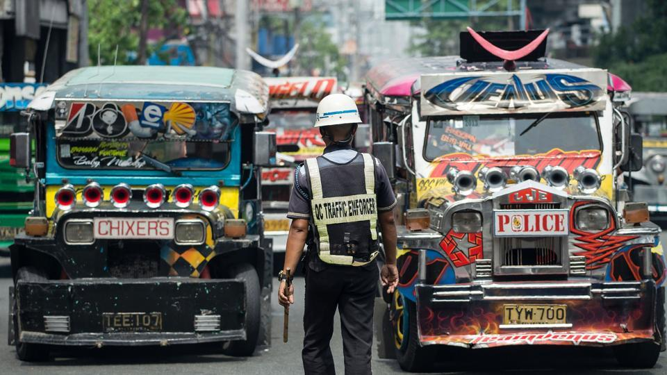 Jeepneys are seen as an enforcer manages traffic at a busy street in Manila.