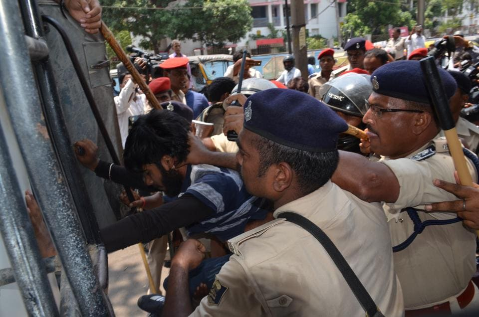 Policemen try to control  students protesting poor results in Bihar board exams in Patna.