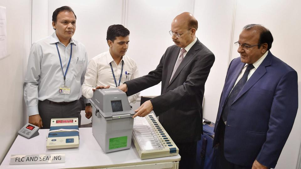 Chief Election Commissioner Nasim Zaidi along with other officials look into an EVM and VVPAT in New Delhi.