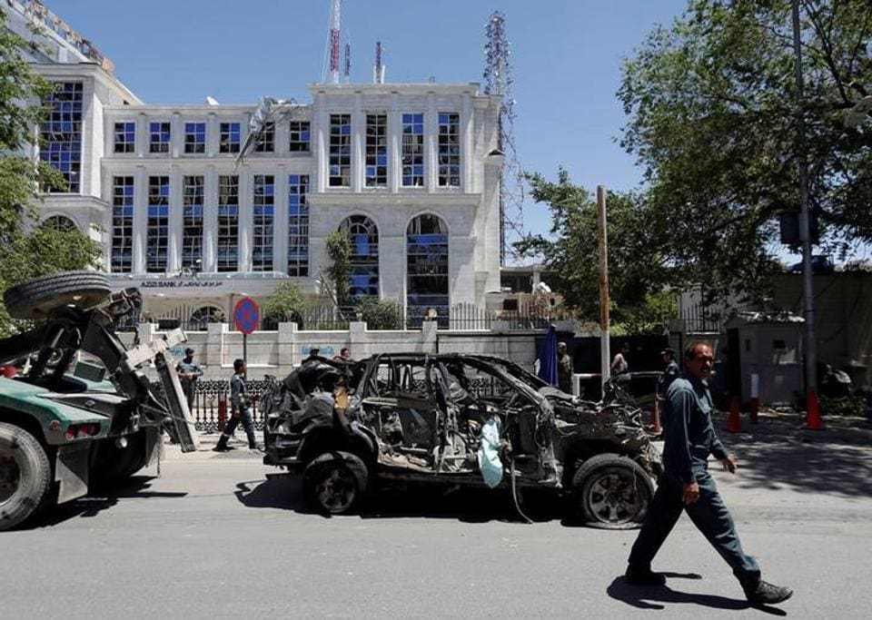 An Afghan policeman past walked next to a damaged vehicle after a blast in Kabul, Afghanistan.