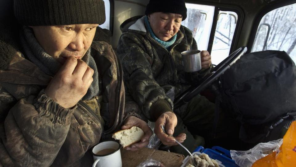 Lumberjacks Alexey Egorov, 45, (L) and Semion VInokurov, 53, lunch in the cabin of their truck in forest outside Tomtor . (Maxim Shemetov / REUTERS)