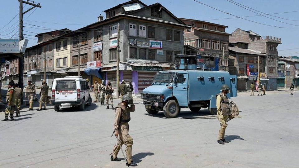 Police and CRPF personnel stand guard in Batamaloo area of Srinagar on May 16, 2017.