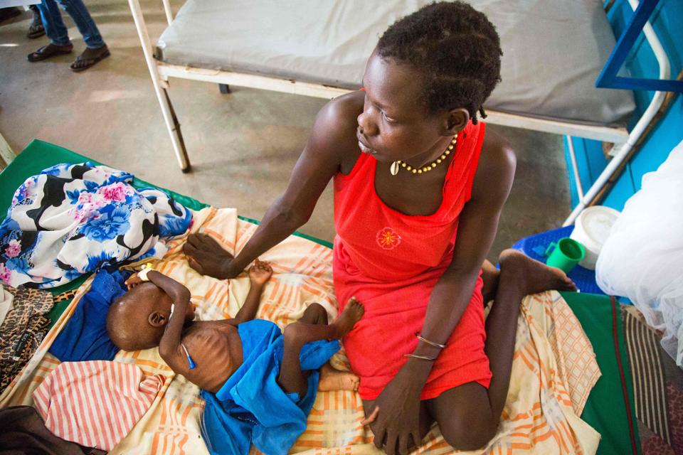 Awien Akol sits next to her one-year-old malnourished child at the Intensive Care Unit of the clinic run by Doctors Without Borders (MSF) in Aweil, Northern Bahr al Ghazal.  (Albert Gonzalez Farran / AFP)