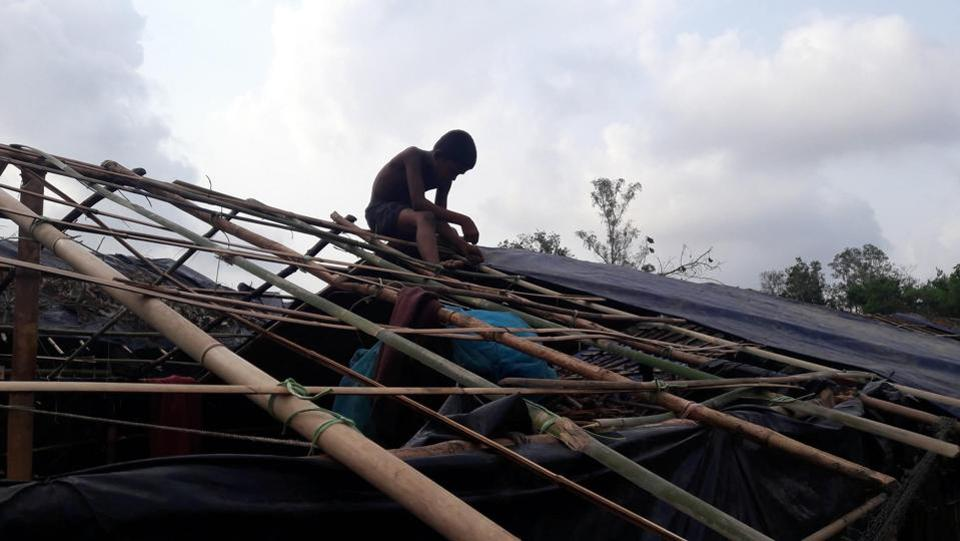 A Rohingya refugee works on rebuilding  his house, which was destroyed as a result of the cyclone.  (AFP)