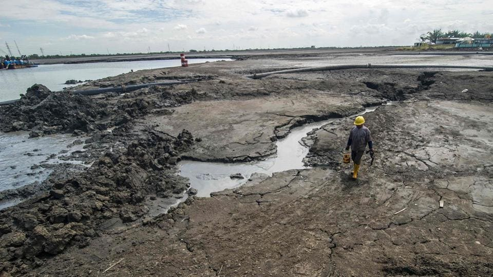 An Indonesian man working at the mud volcano incident area in Sidoarjo, East Java.  Today, the devastated wasteland has become a dark and unlikely tourist attraction, drawing visitors keen to witness the ongoing flow of mud that may never be fully contained. (JUNI KRISWANTO / AFP)