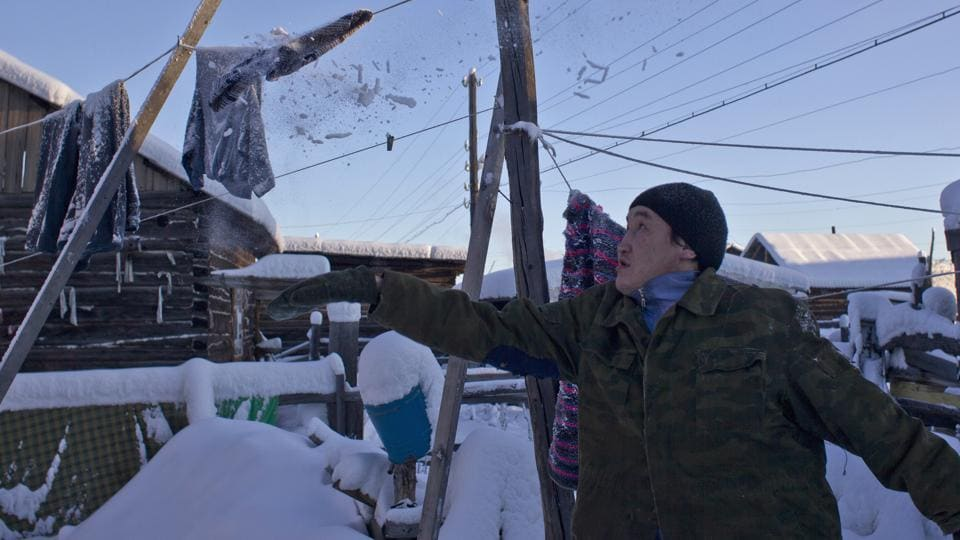 Igor Vinokurov, 35, knocks snow and ice off a frozen washing line in the village of Oymyakon. (Maxim Shemetov/ REUTERS)