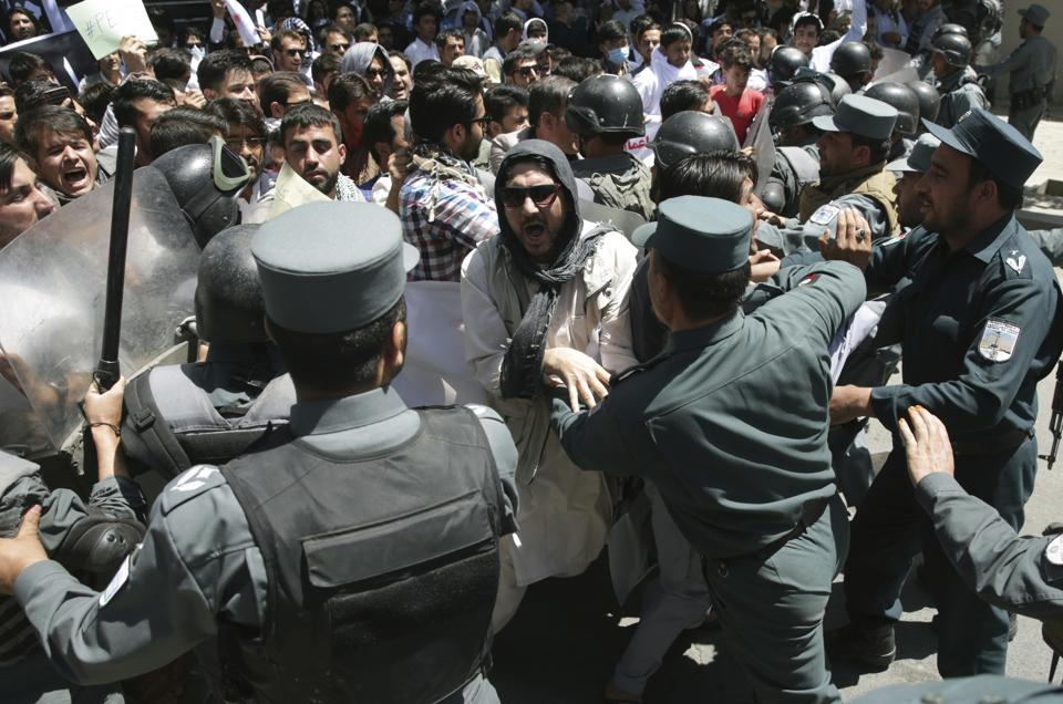 Police forces clash with protesters during a demonstration in Kabul on Friday.