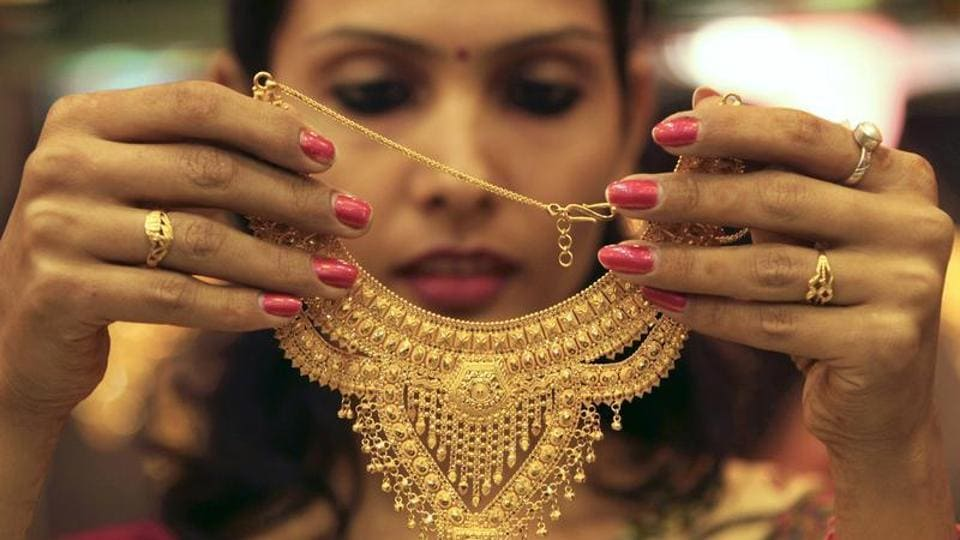 A salesgirl shows a gold necklace to customers at a jewellery showroom in the northern Indian city of Chandigarh.
