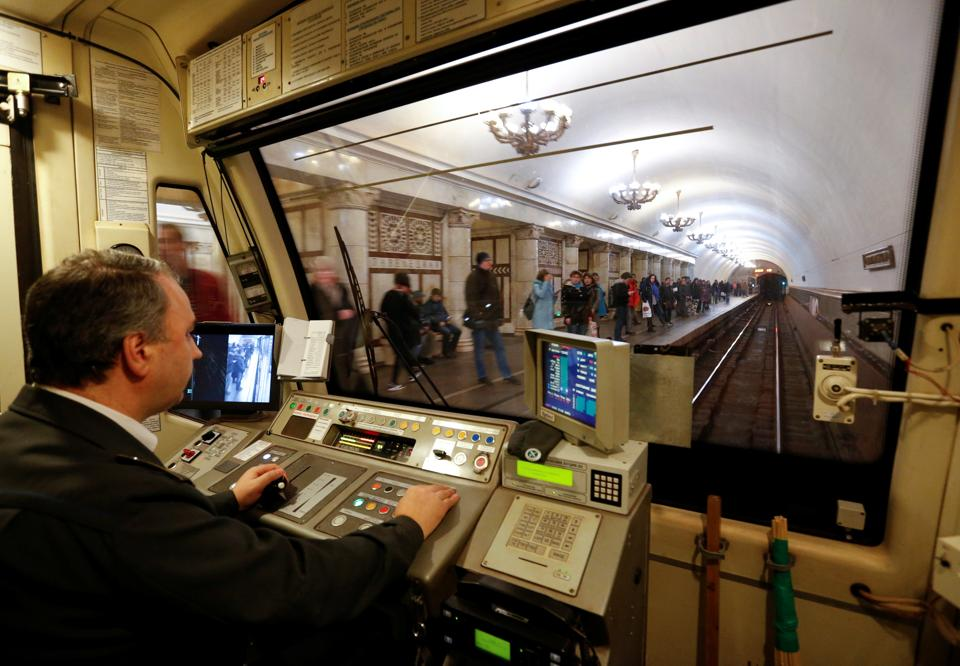 A Moscow metro employee drives a train through a metro station. The Moscow metro's immaculate stations are a mix of old and new. (REUTERS)