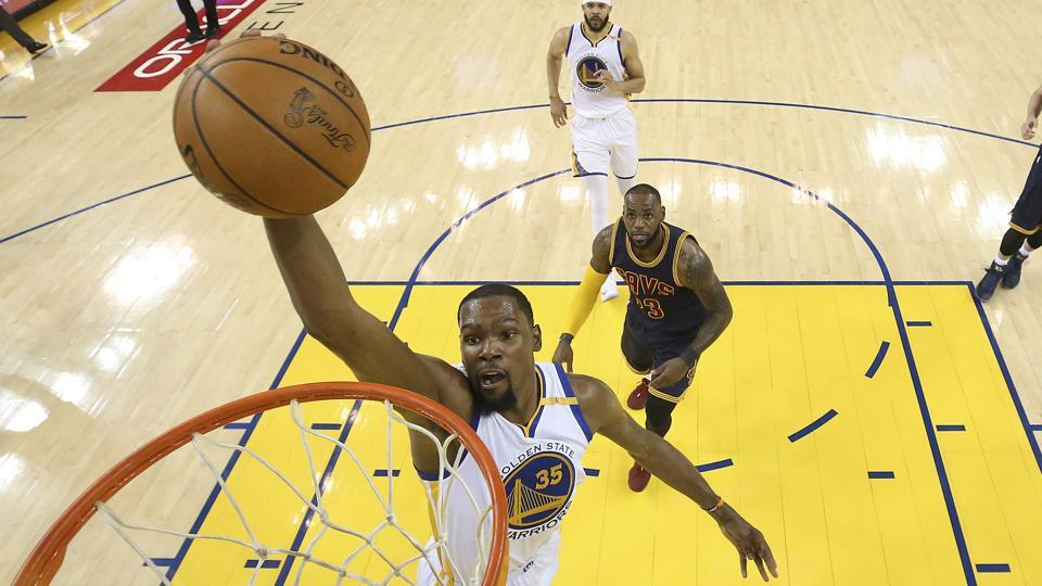 Golden State Warriors forward Kevin Durant dunks in front of Cleveland Cavaliers forward LeBron James during the NBAFinals.