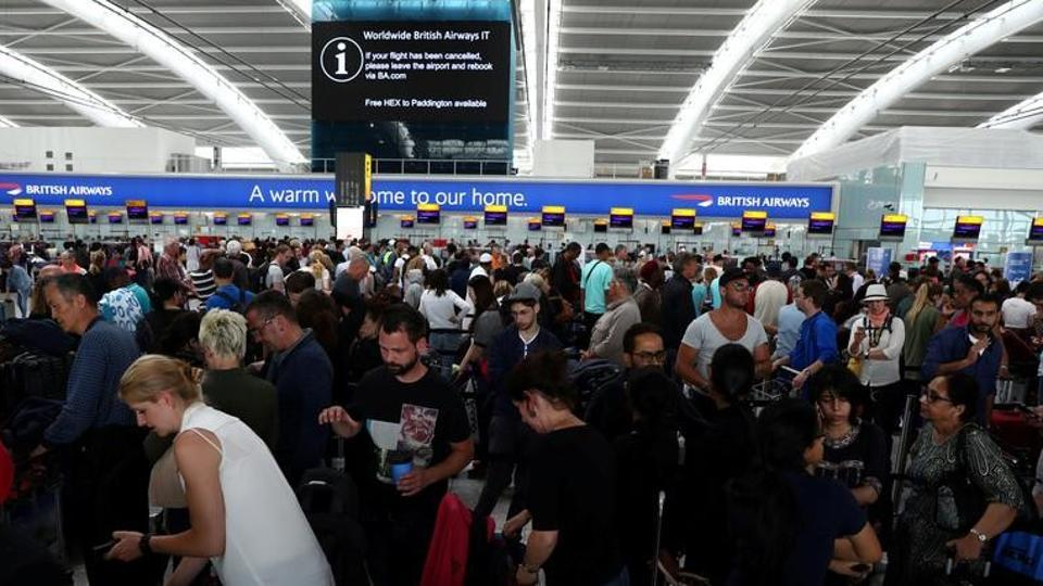 People wait with their luggage at the British Airways check in desks at Heathrow Terminal 5 in London.