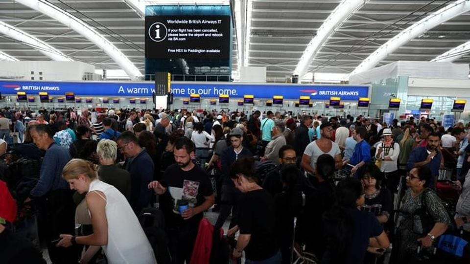 People wait with their luggage at the British Airways check in desks at Heathrow Terminal 5 in London, Britain.