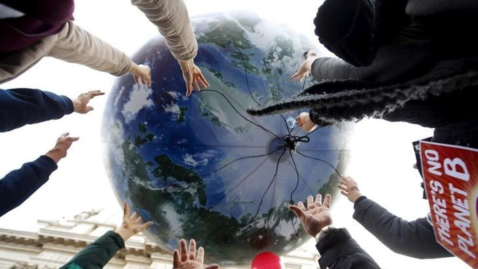 Protesters throw up a globe-shaped balloon during a rally held the day before the start of the 2015 Paris World Climate Change Conference, known as the COP21 summit, in Rome, Italy.