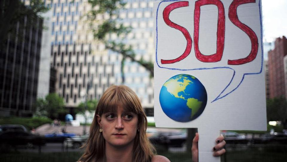 A woman displays a placard during a demonstration in New York on June 1, 2017, to protest US President Donald Trump's decision to pull out of the 195-nation Paris climate accord deal. US President Donald Trump earlier announced America is