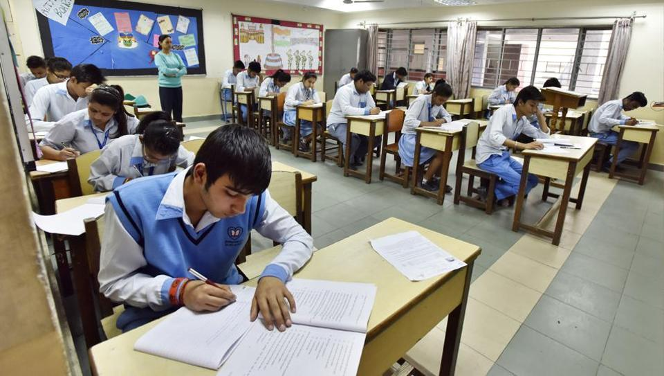 Students of class 12 attending exam during the first day of the CBSE exam at a centre.