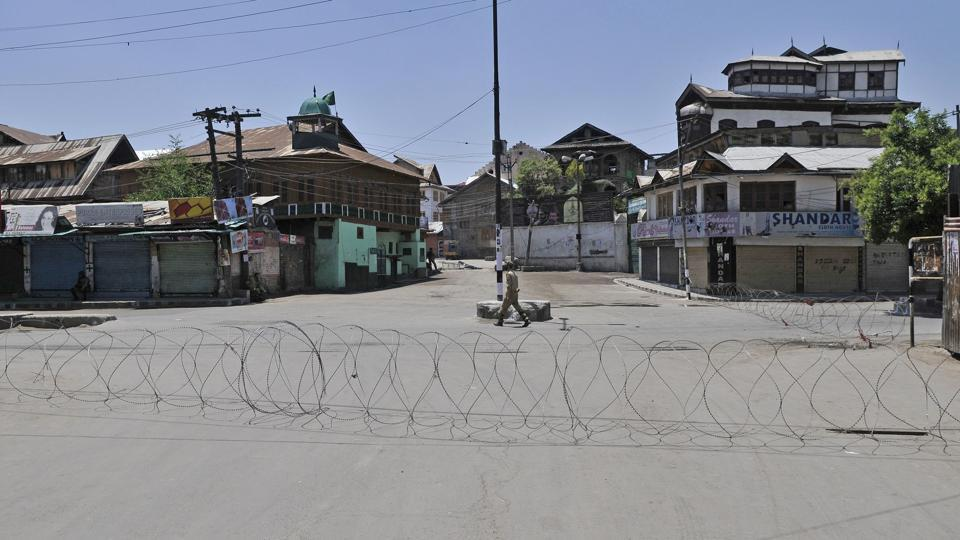A policeman patrols near barbed wire set up as a barricade during curfew in downtown area of Srinagar.