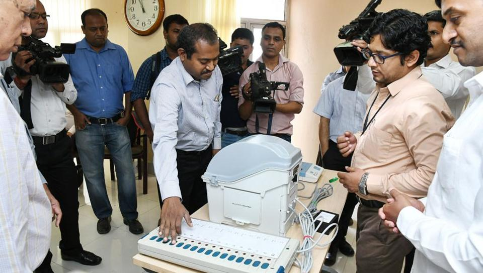 CPI-M representatives check out an EVM machine during the 'open challenge' in New Delhi on Saturday.