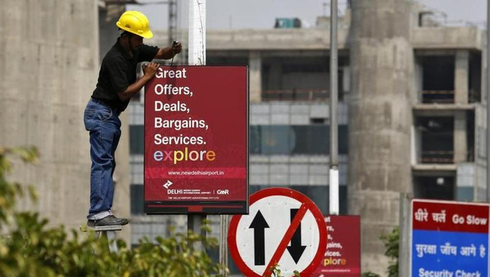 A worker removes a GMR Infrastructure board near to the airport in New Delhi.