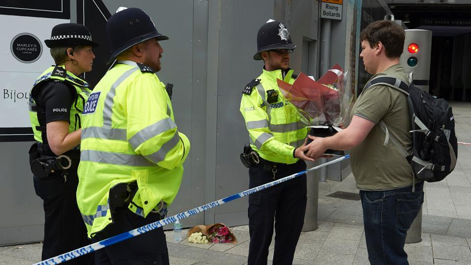 A man asks a police officer to lay flowers outside The Shard in the London Bridge quarter in London on June 4, 2017, as a tribute to the victims of the June 3 terror attack.