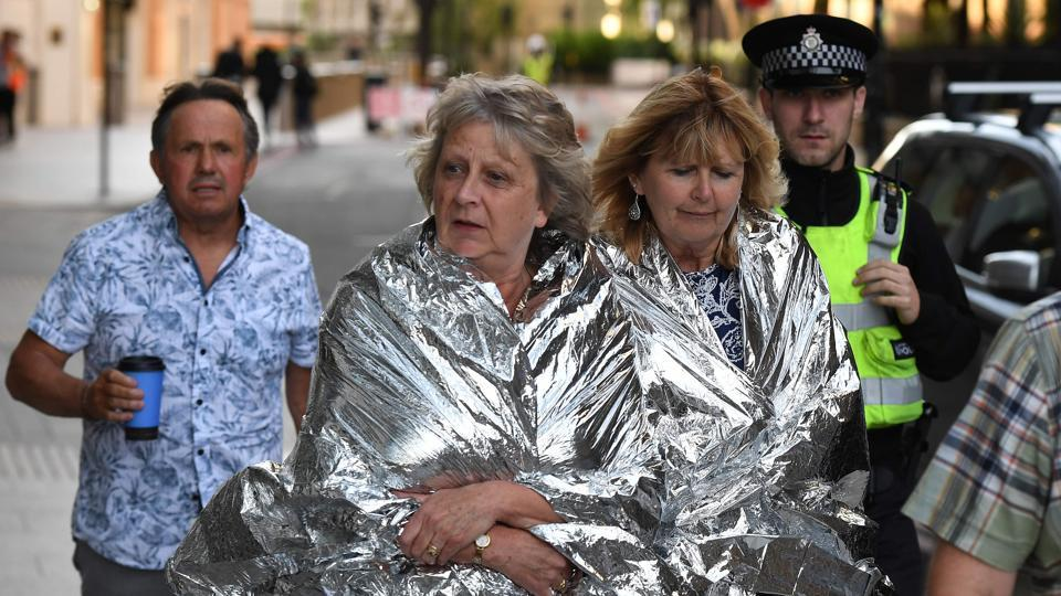 A police officer escorts members of the public, wrapped in foil blankets, towards The Shard in London on June 4, 2017, following a terror attack. Forty-eight people have been taken to hospital after a terror attack in central London in which six people died, the London Ambulance Service said Sunday.