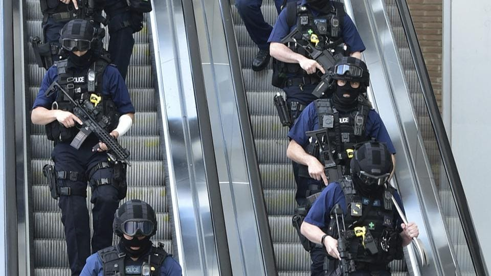 Armed police descend an escalator at the foot of the Shard outside London Bridge station, Sunday June 4,  near the scene of Saturday night's terrorist incident on London Bridge and at Borough Market.