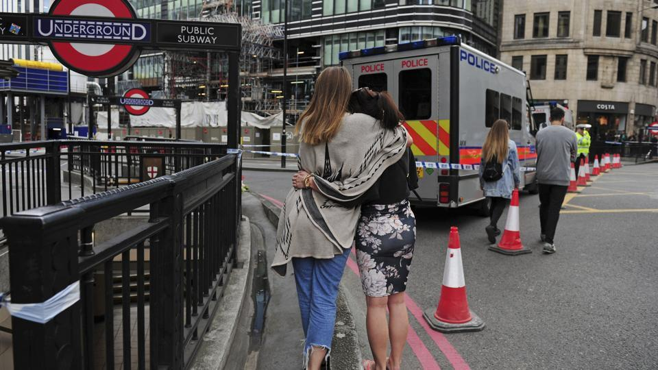 Two women hug after bringing flowers to add to tributes laid on the north side of London Bridge following last night's terrorist incident, Sunday, June 4, 2017.