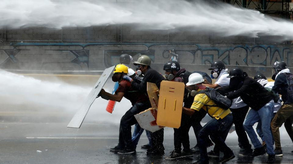 Demonstrators clash with riot security forces while rallying against Venezuela's President Nicolas Maduro in Caracas, Venezuela. (Carlos Garcia  / REUTERS)
