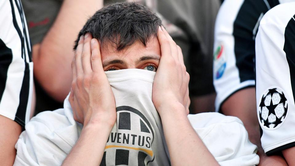 A Juventus' fan holds his face as he watches on a giant screen the Champions League match against Real Madrid.