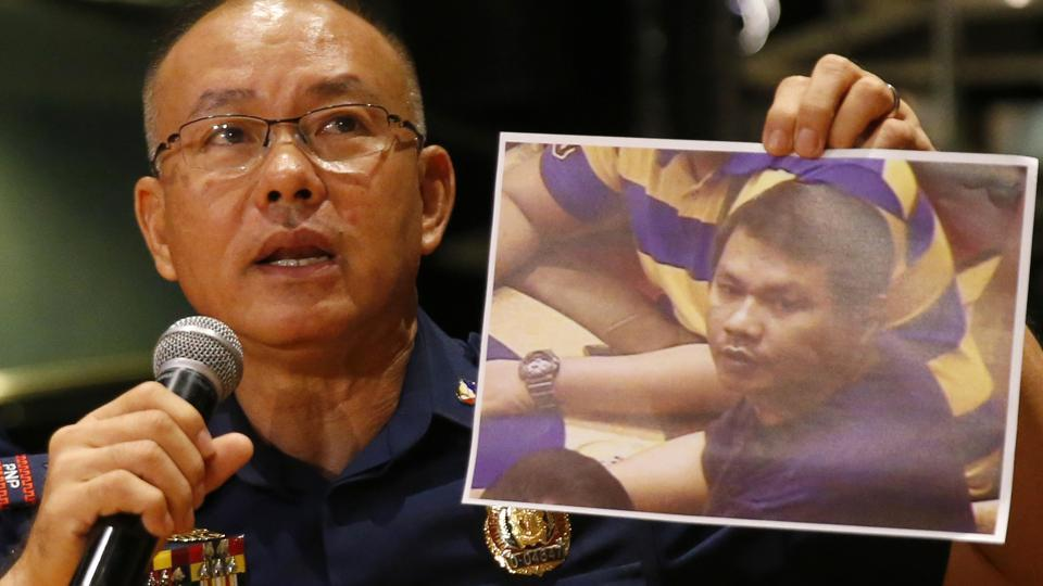 Police Gen. Oscar Albayalde holds a copy of an image of a gunman who stormed the Resorts World Manila complex whom he identified as Jessie Carlos during a news conference Sunday, June 4, 2017 . The lone suspect behind a deadly attack on the casino and shopping complex in Manila was a heavily indebted Filipino, not a terrorist, police said.