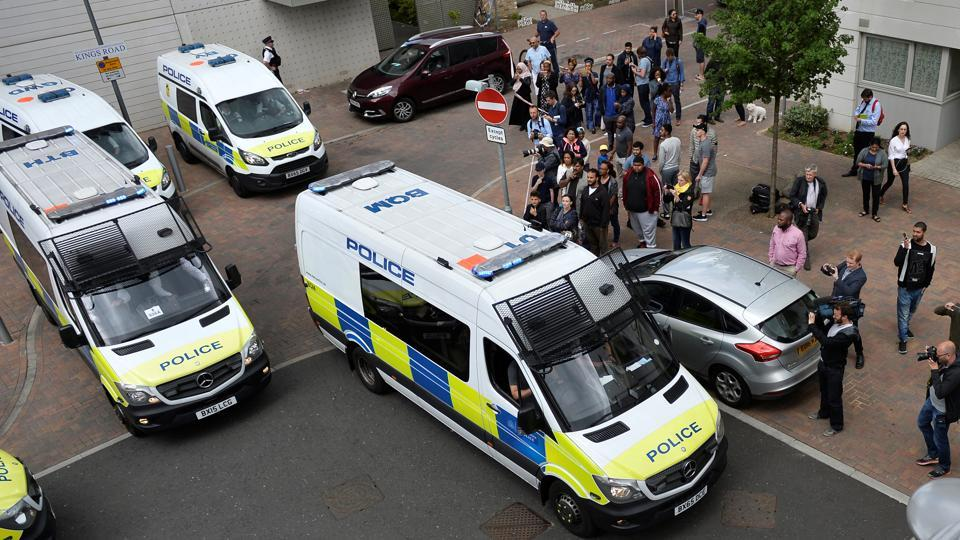 Police vans leave carrying a number of women who were detained after a block of flats was raided in Barking, east London, Britain, June 4, 2017.