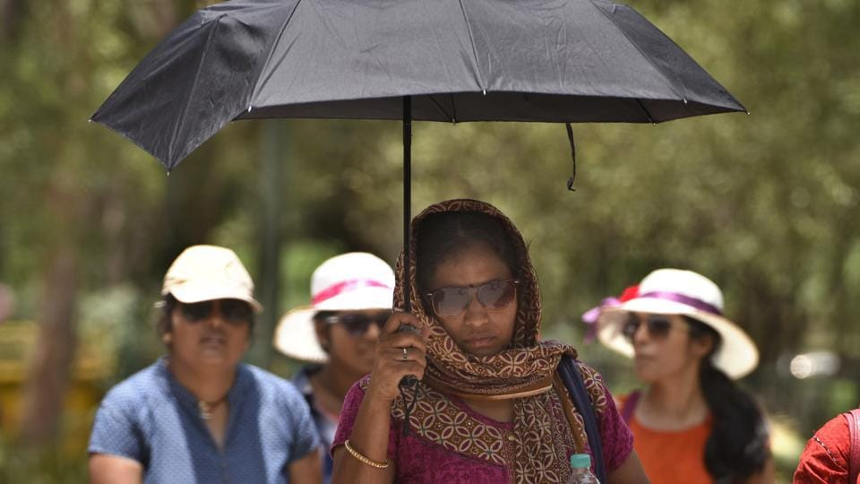 People wear protective gears to beat the heat near Raj Ghat in New Delhi on Sunday. (Sushil Kumar/HT PHOTO)