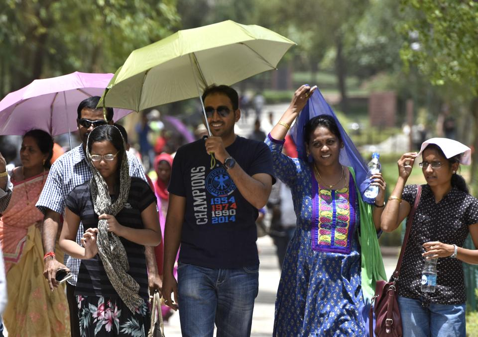 People protect themselves from scorching heat on a hot sunny day near Raj Ghat in New Delhi on Sunday. (Sushil Kumar/HT PHOTO)