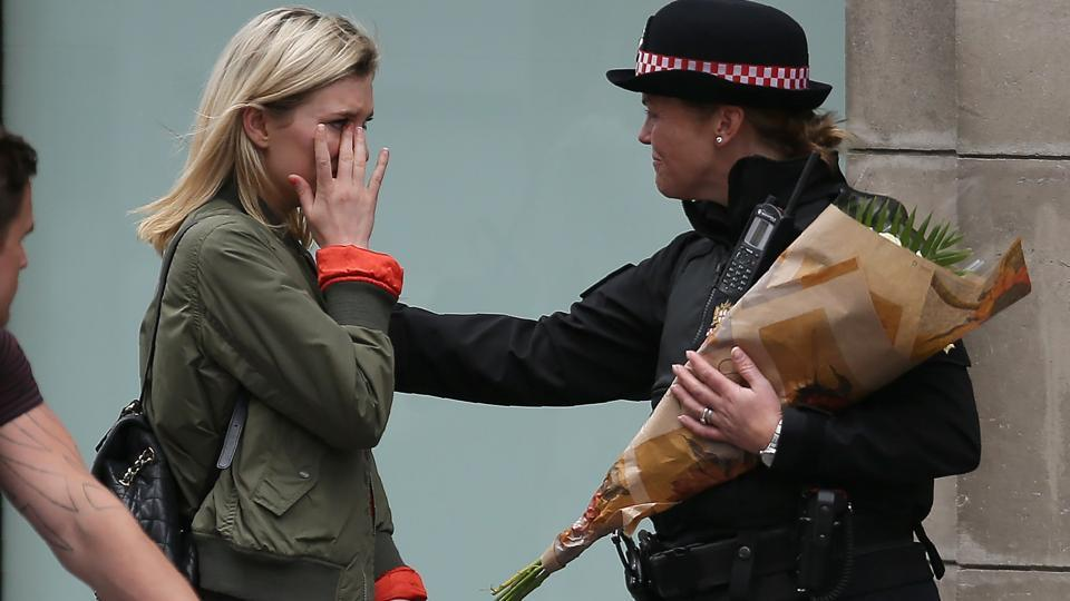 A woman reacts after asking a police officer to lay flowers near London Bridge in London on June 4, 2017, as a tribute to the victims of the June 3 terror attack.
