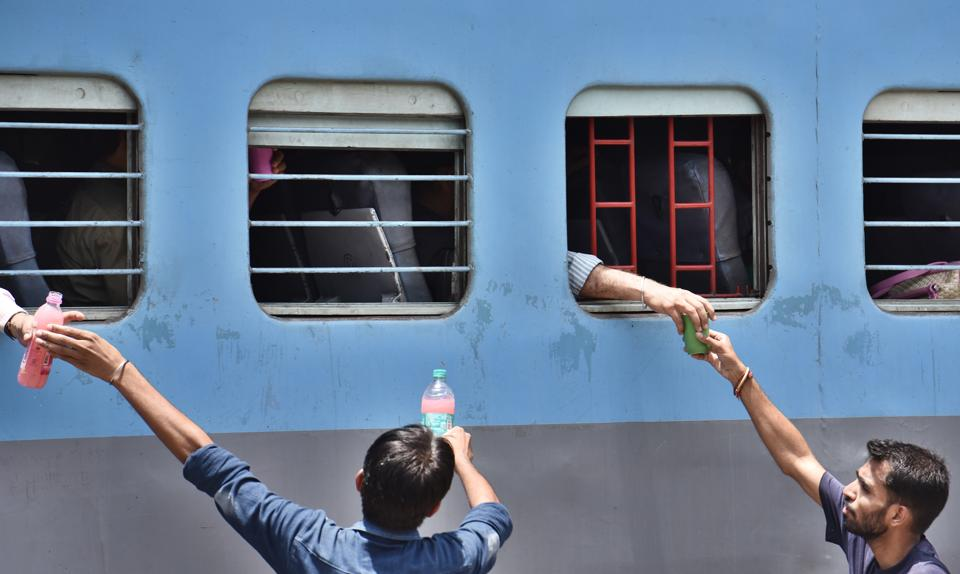 Activists distribute drinking water to passengers at Gurgaon Railway station as the temperature soared to 47°C in Gurgaon on Sunday.