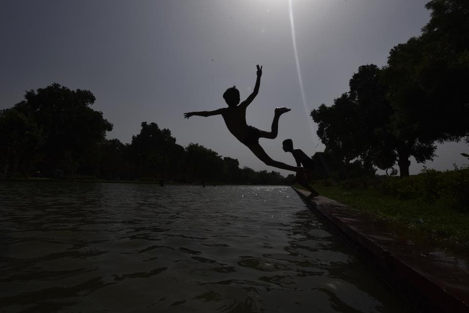 Boys jump into a water body to get relief from heat wave conditions in New Delhi. Temperatures are witnessing a rise in northern part of India, particularly in Delhi, which has recorded the daytime high beyond 45 degrees Celsius in the last 24 hours. (Burhaan Kinu/HT PHOTO)
