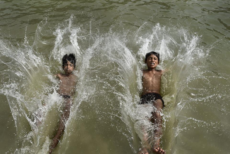 Boys beat the scorching heat in a water body in New Delhi on Sunday. The city recorded a temperature of 44 degrees Celsius on Sunday. (Burhaan Kinu/HT PHOTO)