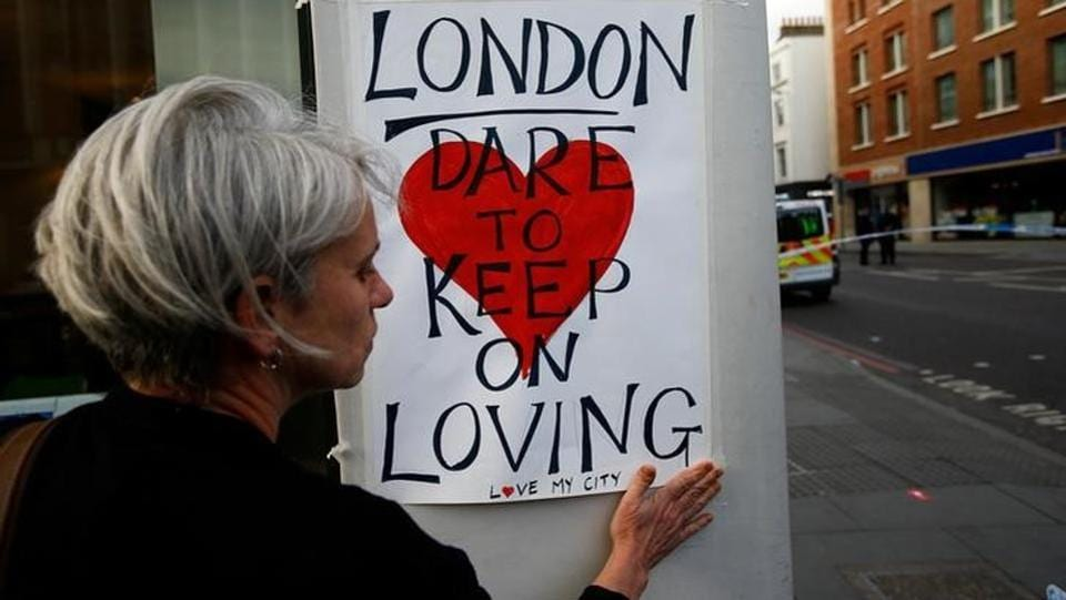 A woman attaches a sign on a street after attackers rammed a hired van into pedestrians on London Bridge and stabbed others nearby killing and injuring people. The attack occurred five days before a parliamentary election and was the third to hit Britain in less than three months.As normal life resumed on Monday after reopening of the bridge, London paid homage to the ones that lost their lives in the terror attack with flowers and slogans of love, strength and unity.   (Peter Nicholls/REUTERS)
