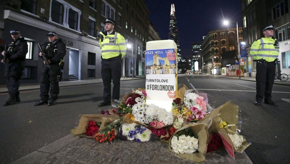 Police officers on duty stand next to floral tributes on Southwark Street in London, on June 4, 2017, near the scene of Saturday's attack.
