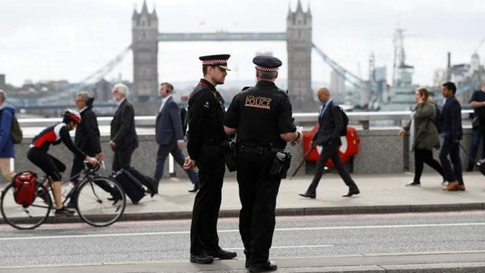 Commuters travel past City of London police officers standing on London Bridge after is was reopened following an attack which left 7 people dead and dozens injured in central London.