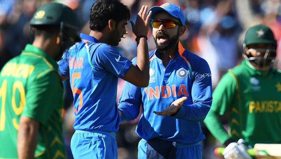 India's Bhuvneshwar Kumar (CL) celebrates the wicket of Pakistan's Ahmed Shehzad with skipper Virat Kohli (CR) during the ICC Champions trophy match against Pakistan.