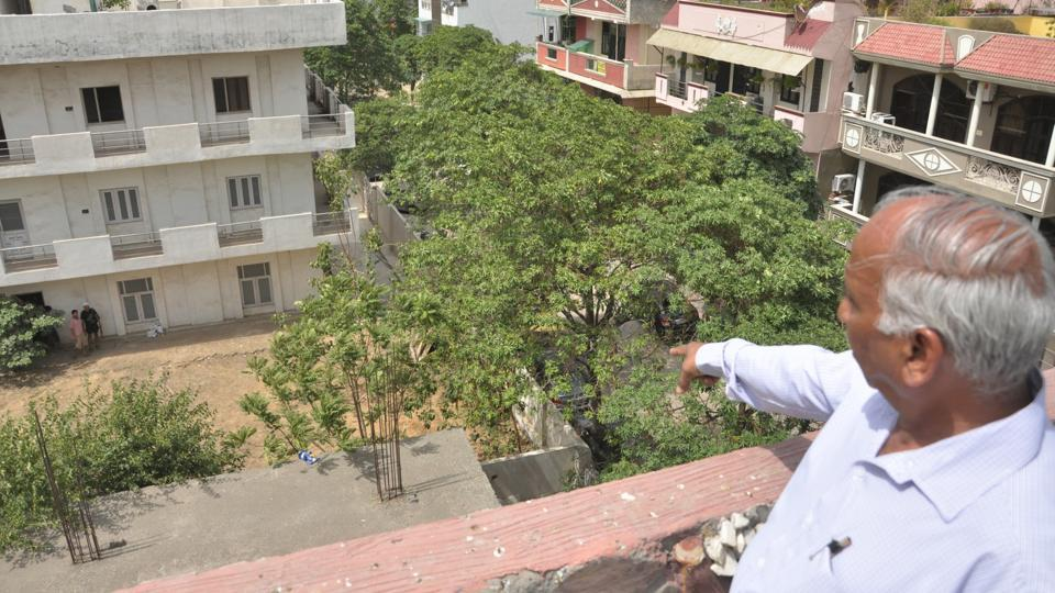 A resident points to the plot in Shakti Khand in Indirapuram, Ghaziabad, where a former IAS  allegedly buried his late wife on Sunday.