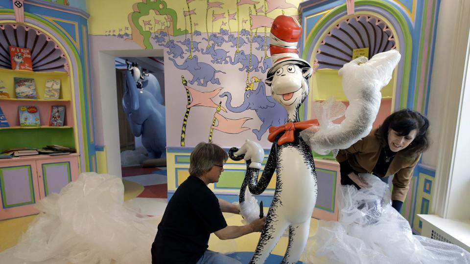 John Simpson (left), project director of exhibitions for The Amazing World of Dr. Seuss Museum, and his wife Kay Simpson, president of Springfield Museums, unwrap a statue of the Cat in the Hat at the museum in Springfield, Massachusetts.