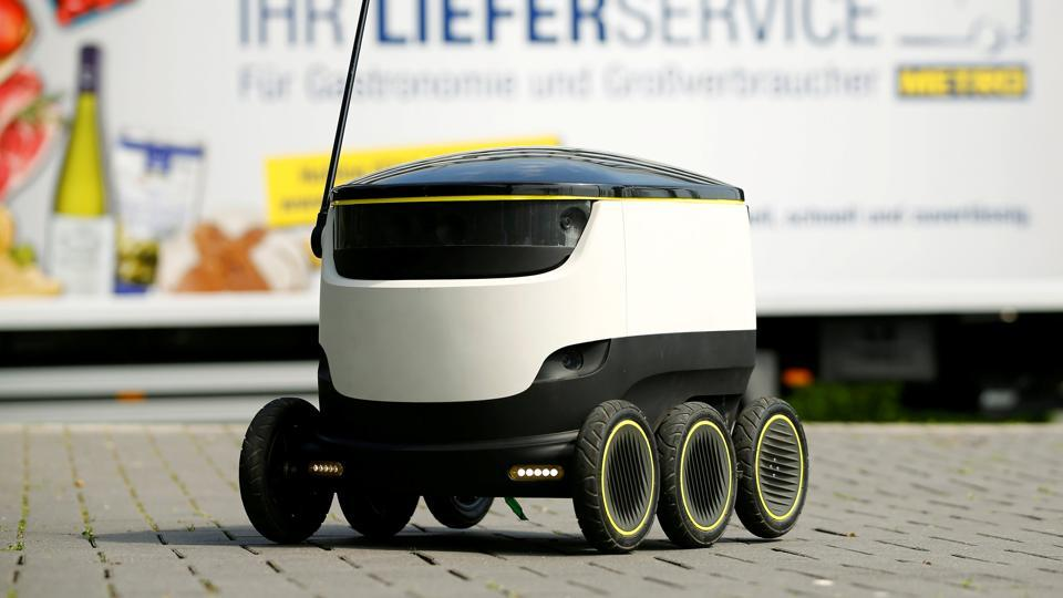 A conventional delivery truck of Germany's biggest retailer Metro AG stands behind the world's first commercial delivery robot of Starship Technologies during a demonstration at Metro's headquarter in Duesseldorf, Germany, June 7, 2016.