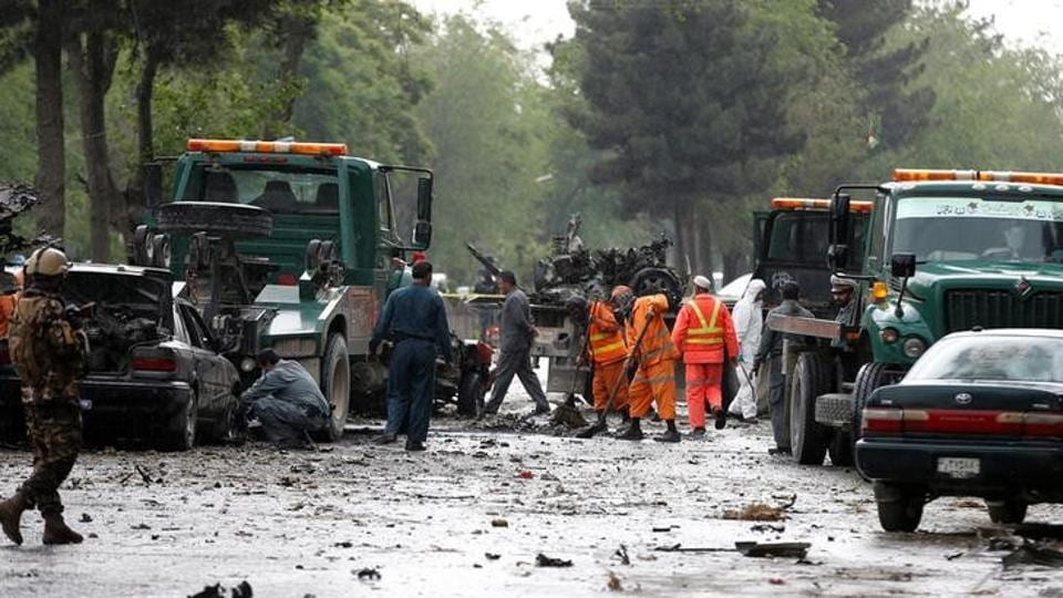 Afghan police and municipal workers clear debris from the site of a suicide bomb attack in Kabul.