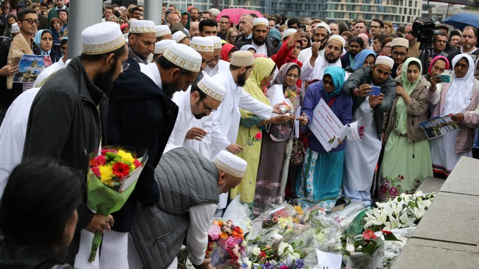 People lay flowers after a vigil to remember the victims of the attack on London Bridge and Borough Market, at Potters Field Park, in central London.