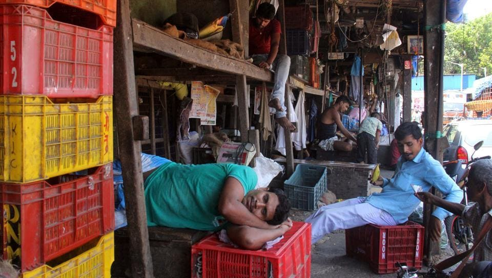 Sellers take a nap at a vegetable market. A paucity in supply to Mumbai has hit businesses.