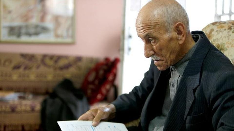 Elderly Palestinian man Abdel-Qader Abu Ajameyah, 81, studies for high school exams, in his home in the West Bank city of Hebron.