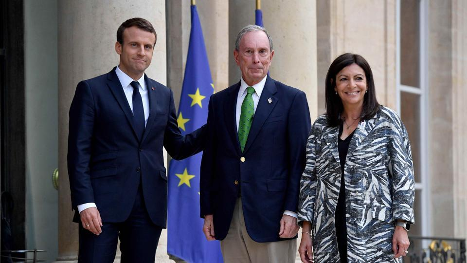 French President Emmanuel Macron (L) and Paris Mayor Anne Hidalgo (R) greet former mayor of New York City Michael Bloomberg (C) in Paris.