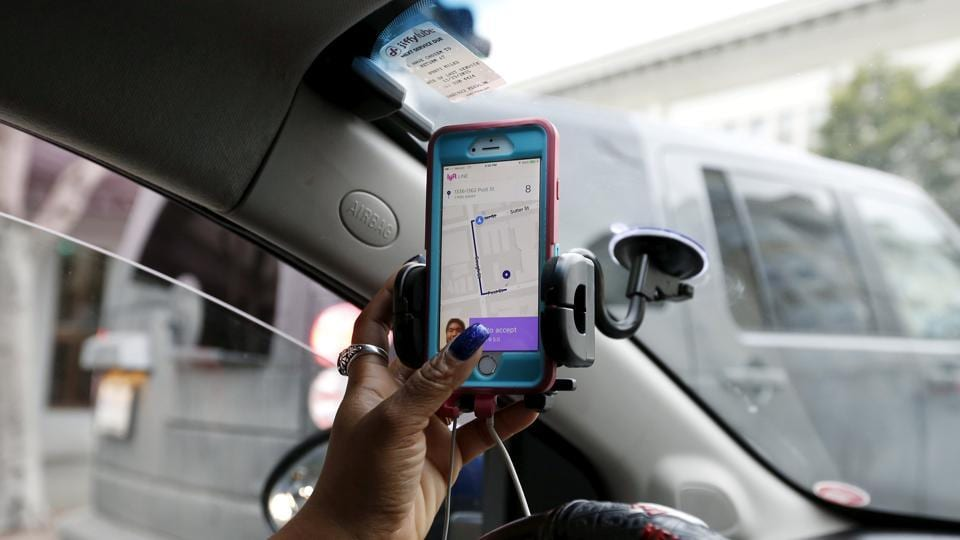 Maya Jackson, a Lyft driver from Sacramento, responds to a ride request on her smartphone during a photo opportunity in San Francisco, California.